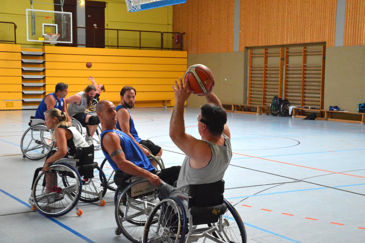 sechs Rollstuhlbasketballer spielen intensiv auf einen Korb Streetball