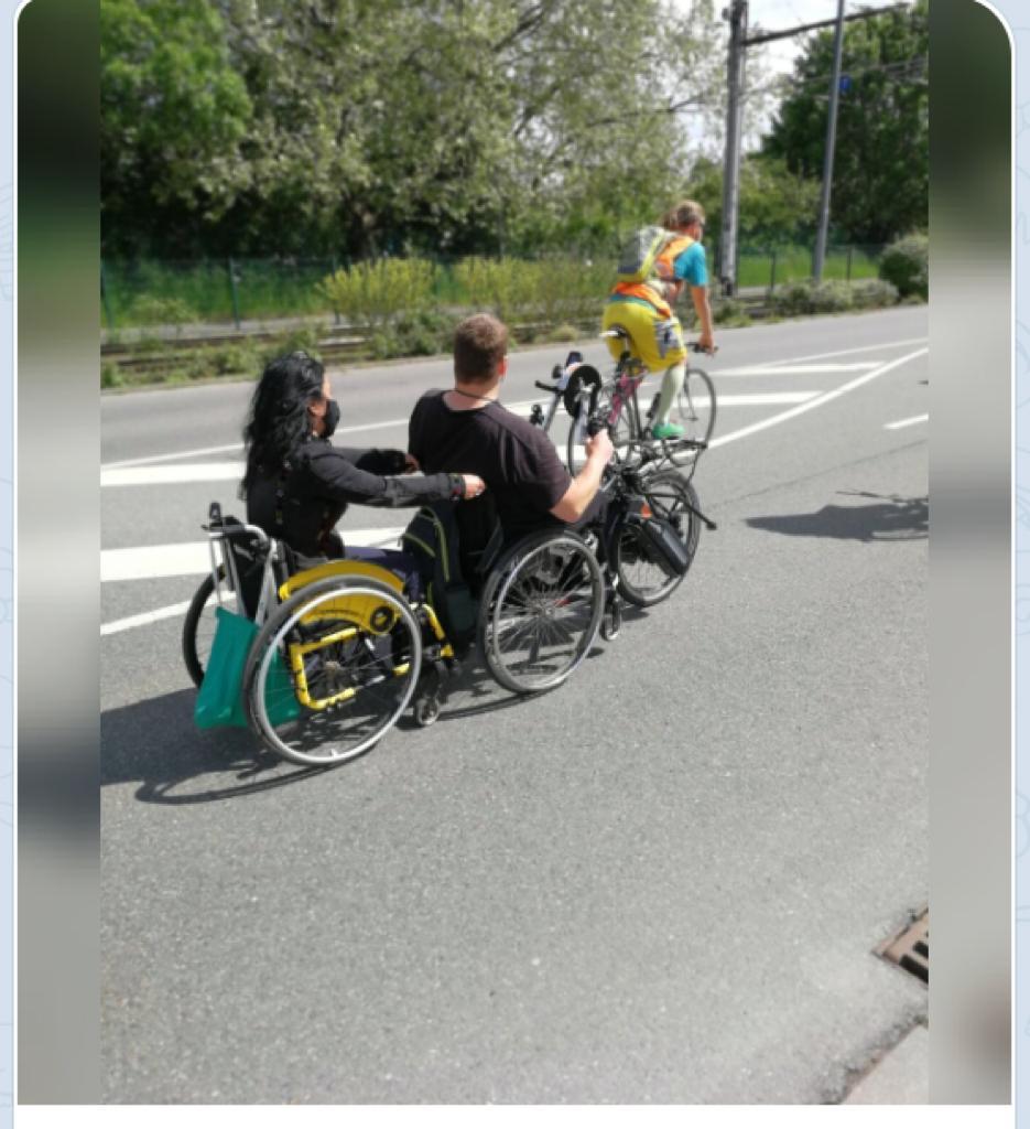 Handbikefahrer zieht eine Rollstuhlfahrerin bei einer Fahrraddemo
